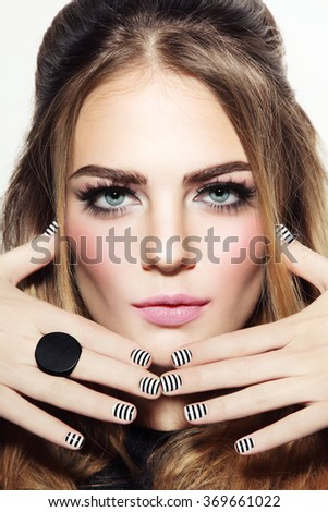 Portrait of young beautiful sexy girl with stylish make-up and striped manicure - stock photo