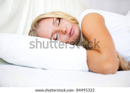 Portrait of young beautiful sleeping woman on bed at bedroom - stock photo