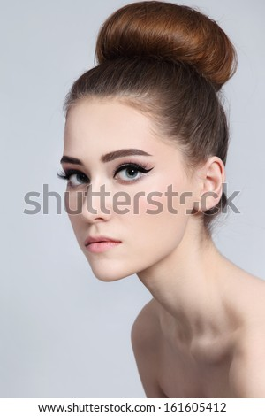Portrait of young beautiful slim girl with cat eyes make-up and hair bun - stock photo