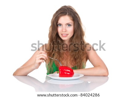 portrait of young beautiful smile woman sitting at the table eat red fresh raw pepper on dish, isolated on white background - stock photo