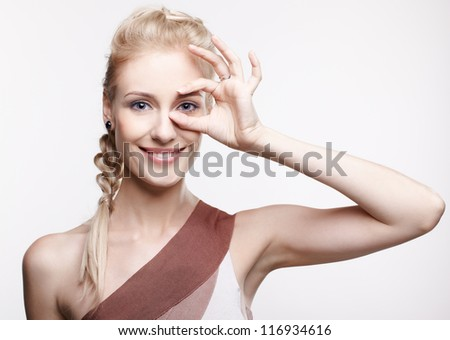 portrait of young beautiful smiling blonde woman on gray - stock photo