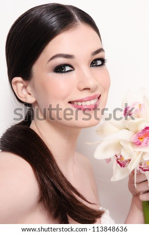 Portrait of young beautiful smiling bride with stylish make-up and orchid bouquet over white wall - stock photo
