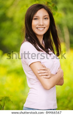 Portrait of young beautiful smiling brunette wearing beige blouse and standing in summer green park. - stock photo