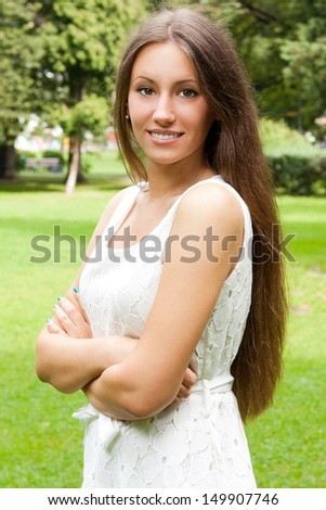 Portrait of young beautiful smiling brunette wearing white dress and standing in summer green park.  - stock photo