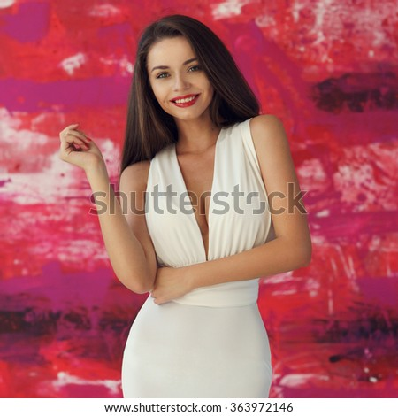 Portrait of young beautiful smiling girl wearing white evening dress with decollete, posing against stylish red background and looking at you - stock photo