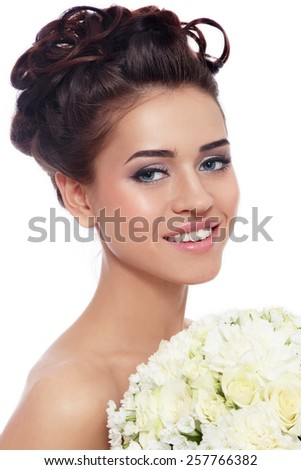 Portrait of young beautiful smiling happy bride with stylish make-up and hairdo over white background - stock photo