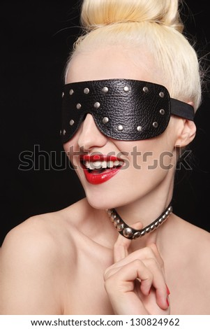 Portrait of young beautiful smiling woman in studded blindfold and collar - stock photo