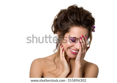 Portrait of young beautiful smiling woman touching her face over white background. Bridal coiffure and pink wedding make-up. Pink lips, smokey eyes and manicure. Copy space - stock photo