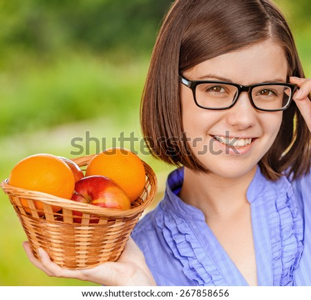 Portrait of young beautiful smiling woman wearing eyeglasses and blue blouse holding basket full of ripe juicy fruits at summer green park. - stock photo