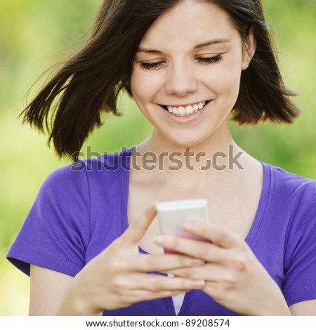 Portrait of young beautiful smiling woman wearing violet blouse with mobile phone at summer green park. - stock photo