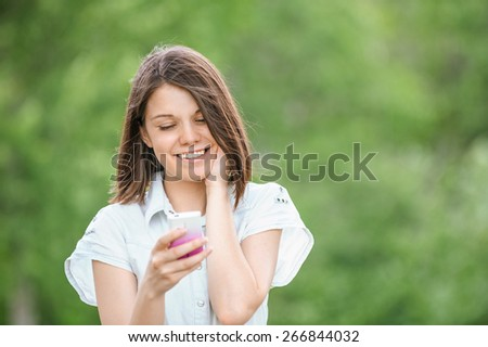 Portrait of young beautiful smiling woman wearing white blouse with mobile phone at summer green park. - stock photo