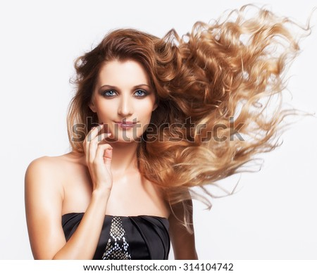 Portrait of young beautiful smiling woman with curly shaggy fly-away hair on gray background