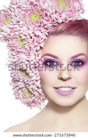 Portrait of young beautiful smiling woman with stylish violet make-up and flowers in her hair over white background - stock photo