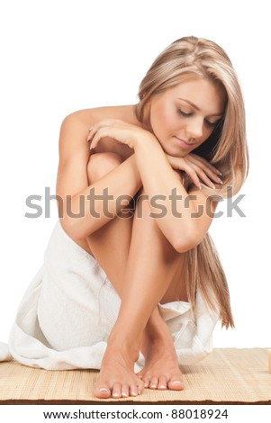 Portrait of young beautiful spa woman  in white towel sitting on bamboo mat and relaxing