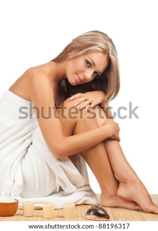 Portrait of young beautiful spa woman sitting on bamboo mat at spa salon - stock photo