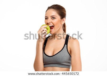 Portrait of young beautiful sportive girl holding apple over white background.