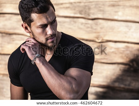 Portrait of young beautiful sporty man in t-shirt against wooden wall.