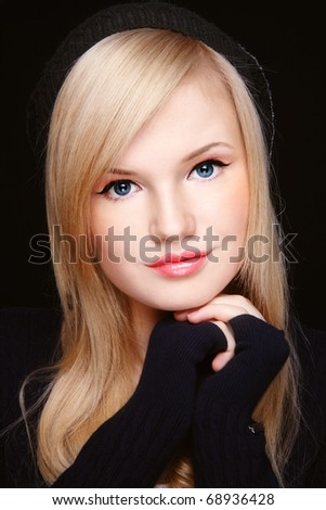 Portrait of young beautiful stylish blond girl in black knitted hat