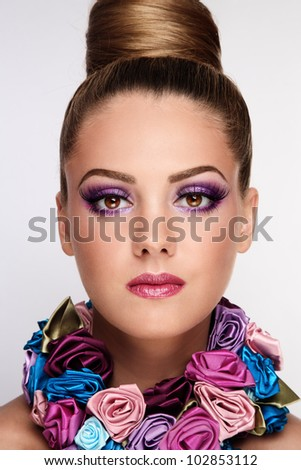 Portrait of young beautiful tanned girl with stylish violet make-up and fancy necklace - stock photo