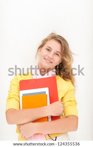 Portrait of young beautiful teenage girl holding file, tablet and notebook isolated on white background. Smiling and happy female student. Study at school, university or college. - stock photo