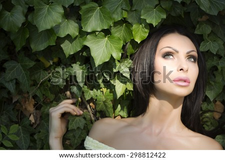 Portrait of young beautiful thoughtful woman with brunette hair and bright makeup looking away standing near green wall of fresh plant leaves in garden outdoor on natural background copyspace - stock photo