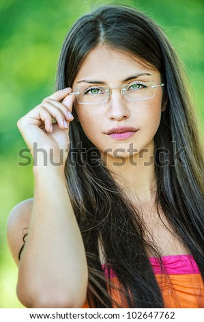 Portrait of young beautiful woman adjusts glasses, on green background summer nature. - stock photo