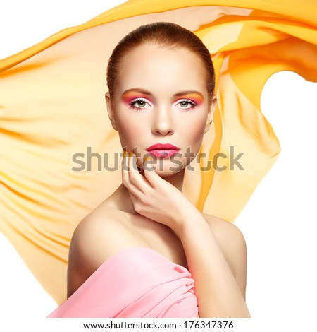 Portrait of young beautiful woman against flying fabric. Beauty woman face closeup. Professional makeup - stock photo