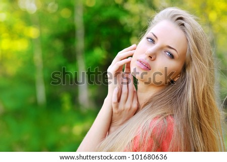 Portrait of young beautiful woman against lake in park