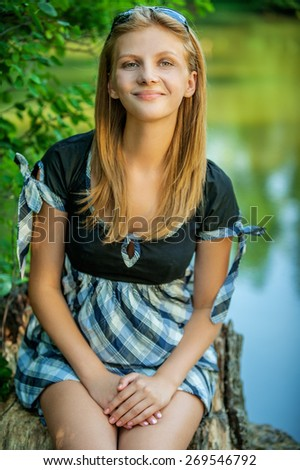 Portrait of young beautiful woman against summer garden. - stock photo