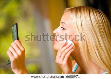 Portrait of young beautiful woman applying creme - stock photo
