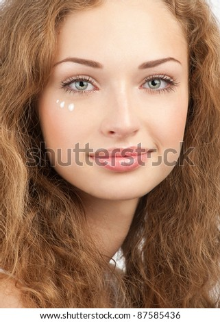 Portrait of young beautiful woman applying moisturizing cream for eyelids, isolated on white background - stock photo