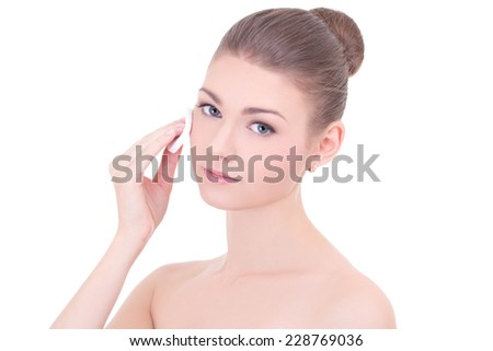 portrait of young beautiful woman cleaning skin by cotton pad isolated on white background - stock photo