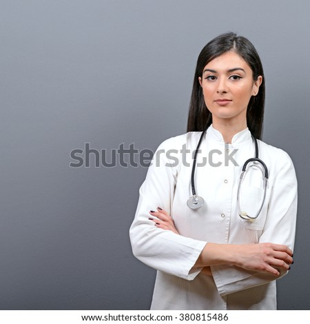 Portrait of young beautiful woman doctor against gray background - stock photo