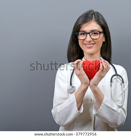 Portrait of young beautiful woman doctor holding red heart against gray background - stock photo