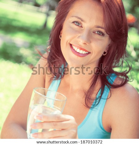 Portrait of young beautiful woman drinking water on picnic at summer green park. Retro retouch photo - stock photo