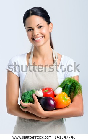 Portrait of young beautiful woman holding raw vegetables in her arms, peppers, broccoli, dill, mushrooms, aubergine - stock photo