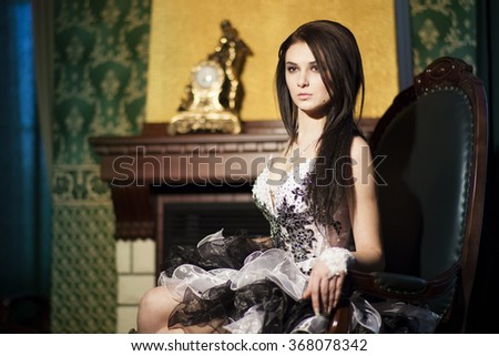 Portrait of young beautiful woman in evening dress sitting in a chair in a luxury interior. Fashion style portrait of pretty lady