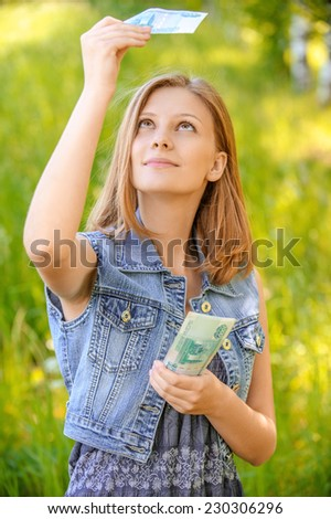 portrait of young beautiful woman in jean jacket counting money at summer green park