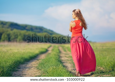 Portrait of young beautiful woman in long red dress standing back on the road in the field outdoor - stock photo
