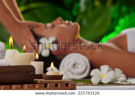 portrait of young beautiful woman in spa environment. focused on candles - stock photo