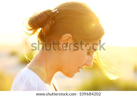 Portrait of young beautiful woman in sunset light - stock photo