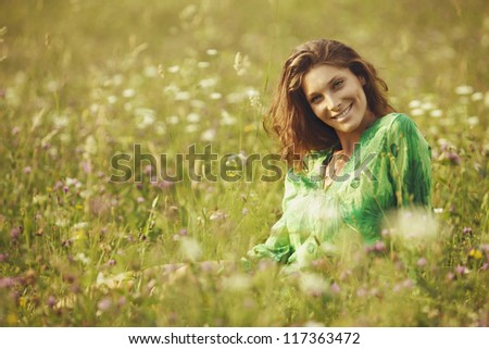 Portrait of young beautiful woman  in the flowers field - stock photo