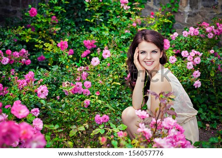 Portrait of young beautiful woman in the rose garden - stock photo