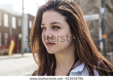 Portrait of young beautiful woman in urban background