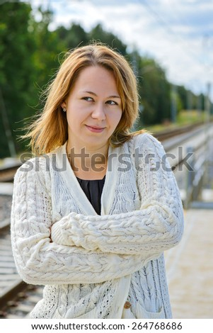 Portrait of young beautiful woman in white cardigan - stock photo