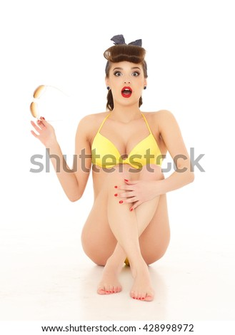 Portrait of young beautiful woman in yellow bikini with sunglasses on a white background. Vacation.