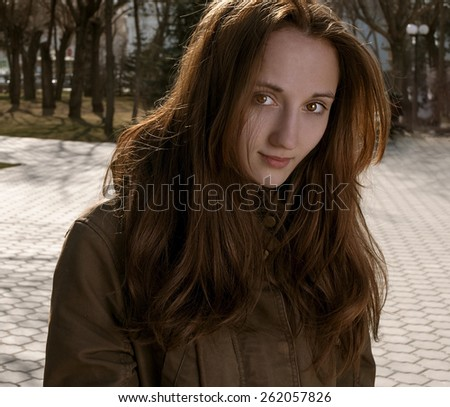 Portrait of young beautiful woman looking at camera in city park at fall or early spring. - stock photo