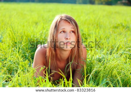 Portrait of young beautiful woman lying on green grass. Looking up