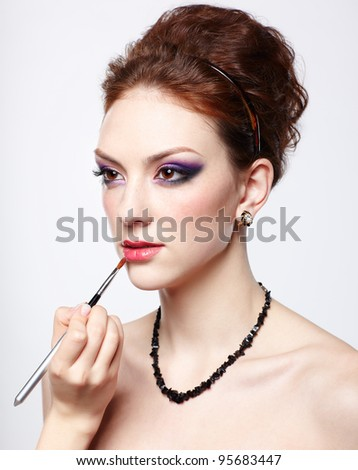 portrait of young beautiful woman maked up by makeup artist's hand putting lipstick on with brush - stock photo