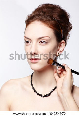 portrait of young beautiful woman maked up by makeup artist's hand putting toner on - stock photo